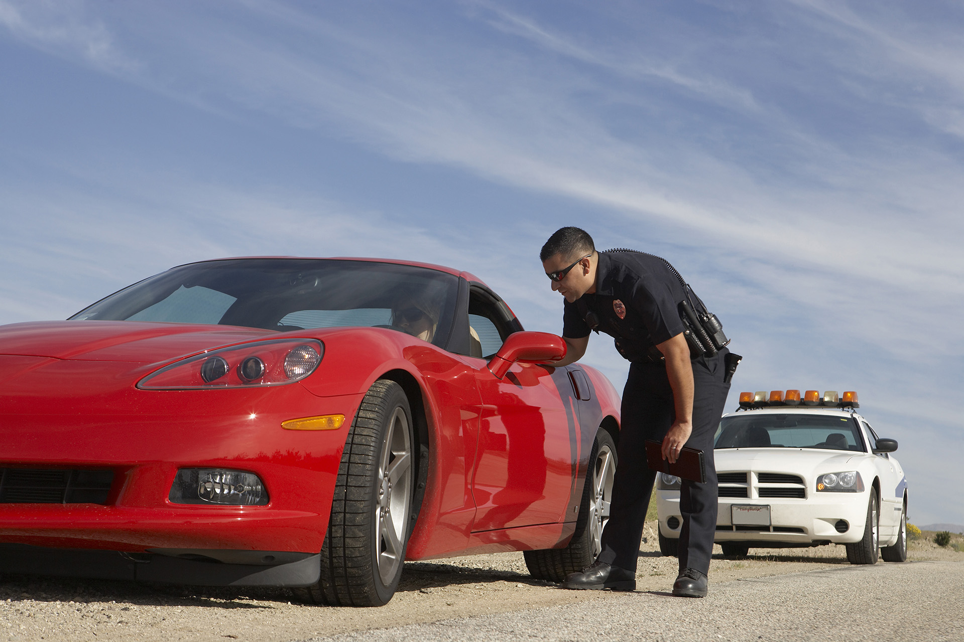 Police Officer Issuing Traffic Ticket to Woman In Red Sports Car